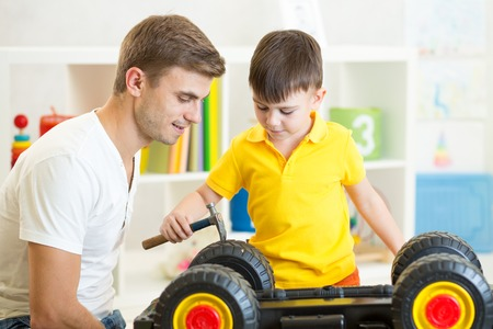 kid boy and his father repair toy lorry in nursery Stock Photo