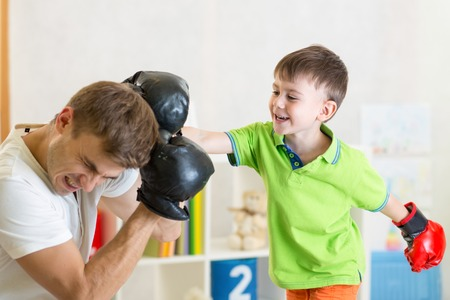 kid and dad play boxing in children room