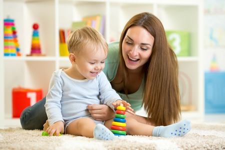 day care center: little child boy and his mommy play with toys at home