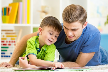 Father and son read together sitting on the floor. Kid boy reading story book with his dad at home.
