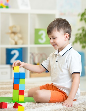 toy: child little boy playing with wooden cubes toys in nursery at home or daycare center Stock Photo