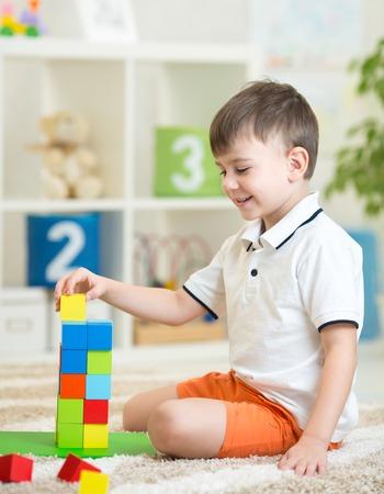 juguete: niño niño jugando con cubos de juguetes de madera en el cuarto de niños en el hogar o centro de guardería