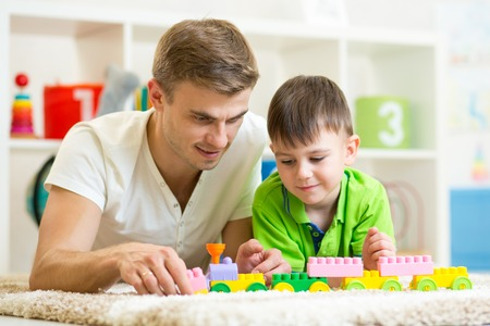 parents with baby: Father and child boy playing construction game together at home.