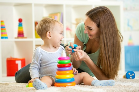 baby playing toy: cute mother and child boy play together indoors at home