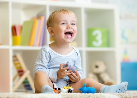 Happy little boy. Smiling child toddler plays animal toys at home or kindergarten.