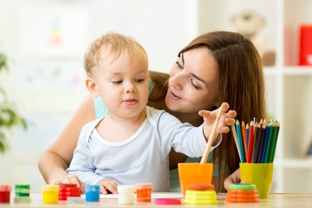 nursery room: cute kid boy painting with paintbrush at home or day care center