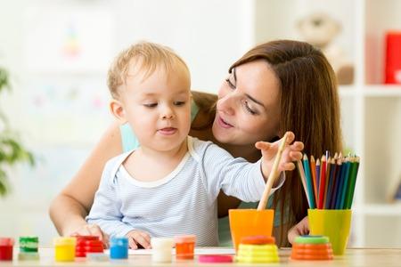 brocha de pintura: lindo pintura niño chico con la brocha en el centro de la casa o la guardería Foto de archivo