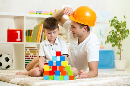 dad: Father and child playing construction game together at home.