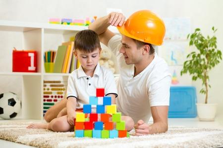personas reunidas: Padre e hijo jugar juego de construcci�n juntos en casa.