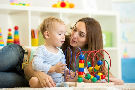 nursery room: child boy and mother playing with educational toy