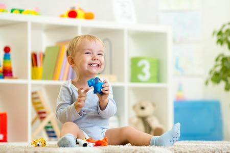 juguetes: feliz niño niño sostiene juguete elefant sentado en el piso en el vivero Foto de archivo