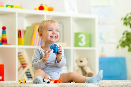 happy child boy holds elefant toy sitting on floor in nursery