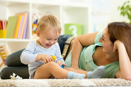 happy child boy holds animal toy playing with mom in nursery