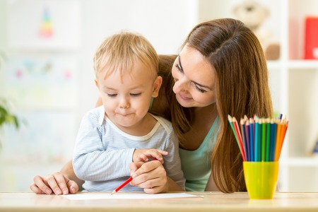 nursery school: adorable kid child boy drawing with mother help Stock Photo