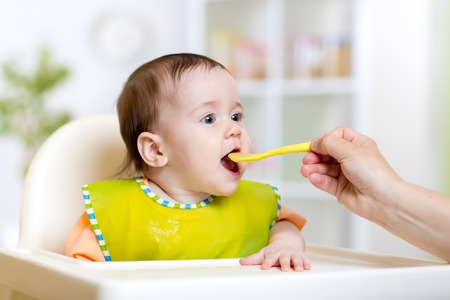 kid girl eating with spoon indoors at kitchen Stock Photo