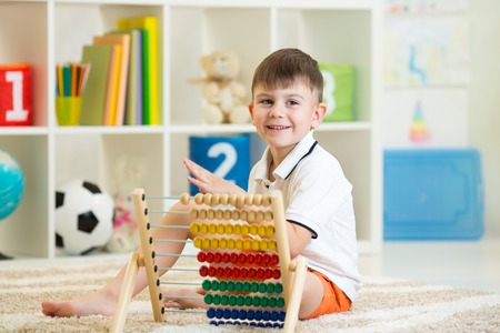 nursery education: happy child boy playing with abacus toy in nursery
