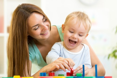 puzzle people: kid and mother playing together with puzzle toy
