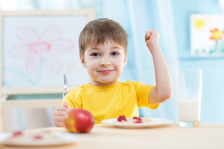 kasha: child boy eats healthy food showing his strength indoors