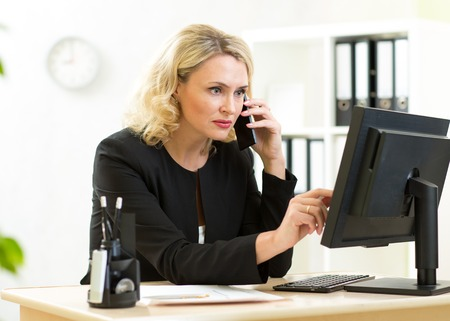 papeles oficina: Middle-aged pretty business woman working at pc in office