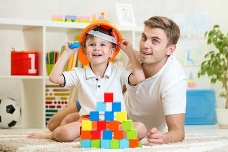 children play: kid boy and father play builders in children room