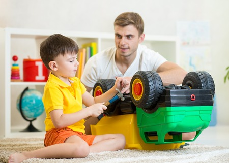 teaching: Child boy playing at home with truck toy closely watched by his father who is leaning over him Stock Photo