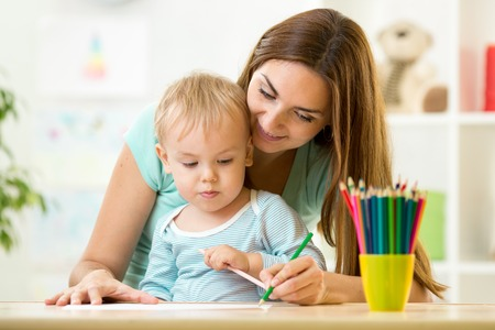 helping: Mother helping her kid son to make drawings Stock Photo