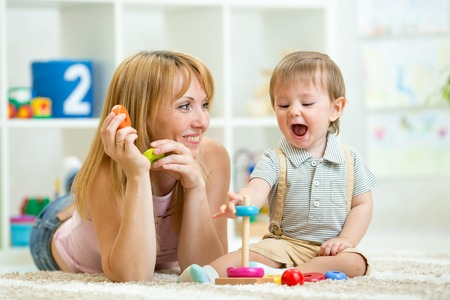 parent and baby boy play together at home