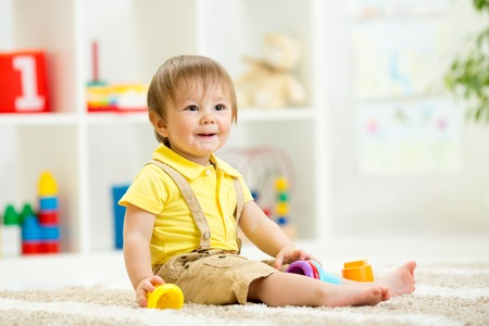day care: Cute little child is playing with toys while sitting on floor in room