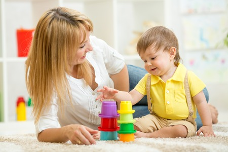 woman sitting floor: mom and child toddler play toys in nursery at home Stock Photo