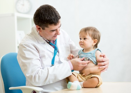 stethoscope: male pediatrician examining heartbeat of baby boy with stethoscope Stock Photo