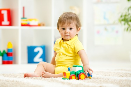 play room: child boy toddler playing with toy car at home