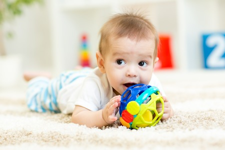 乳幼児: 子供部屋の柔らかな絨毯に横になっているかわいい赤ちゃん