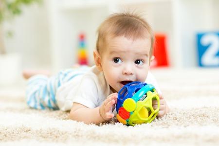 bebe gateando: lindo bebé acostado en la alfombra suave en la habitación de los niños Foto de archivo