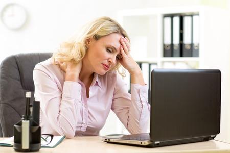 agotado: Cansado de negocios de mediana edad en su oficina de trabajo en equipo