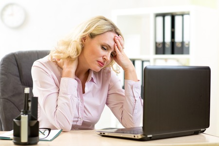 exhausted: Tired middle-aged businesswoman in her office working at computer