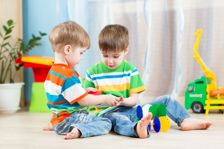 family activities: two kids boys play together with educational toys