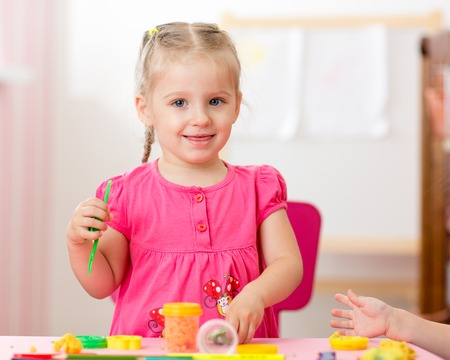child girl drawing and making by hands at nursery or kindergarten Stock Photo
