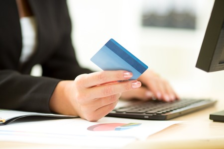 tecnolog�a informatica: Empresaria que sostiene la tarjeta de cr�dito en la mano y entrar el c�digo de seguridad utilizando el teclado del ordenador port�til