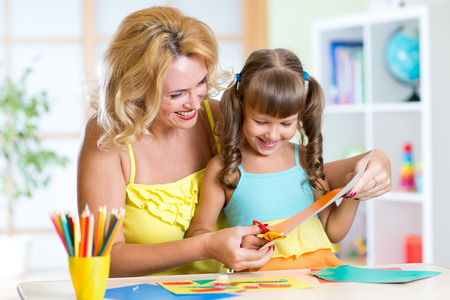 preschool: kid girl and mother cutting at home