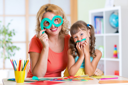 scissors: mother and daughter have a fun cutting from paper