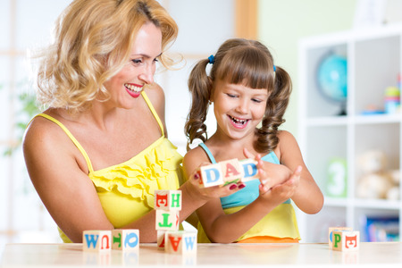 cute kids: Mother and her kids playing with cubes and learning letters