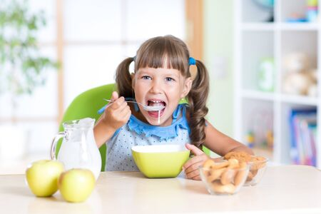 eating yogurt: child girl eating healthy food at home in kitchen Stock Photo