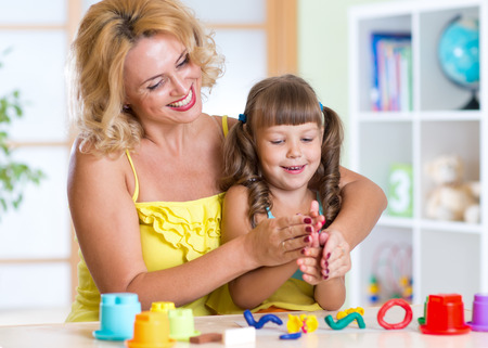 tinkering: mom and daughter play colorful clay toys at home