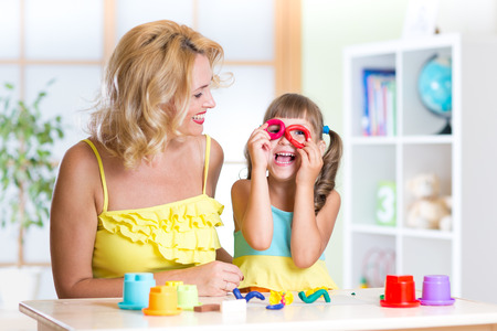 tinkering: woman and kid girl have fun pastime making handcraft at home Stock Photo
