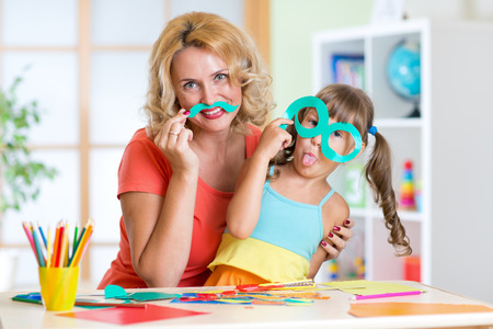 playschool: Child girl with mother have a fun cutting out scissors paper in preschool