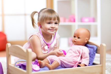 kids playing: Cute Child Playing Doctor with doll Toy