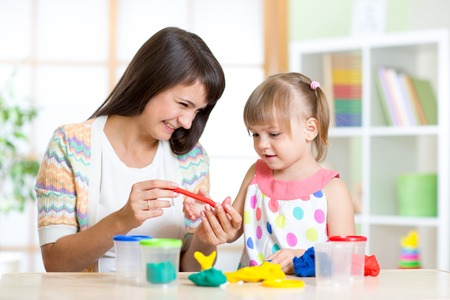 teaching: mother teaches her child to work with colorful play clay toys