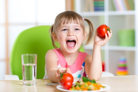 happy child girl eats dinner and shows tomatoes Stockfoto