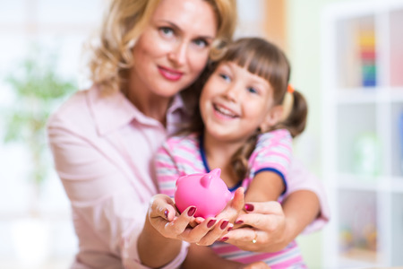 finance girl: family and savings concept - happy mother and child daughter putting money to piggy bank Stock Photo