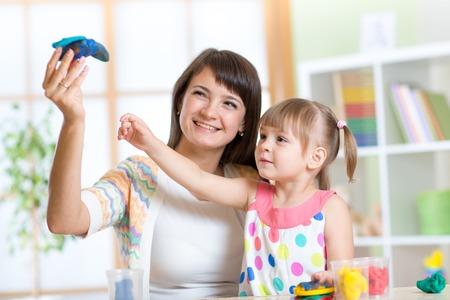 clays: woman teaches child girl handcraft at kindergarten or playschool